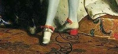 Detalle de los zapatos con el tacón rojo.