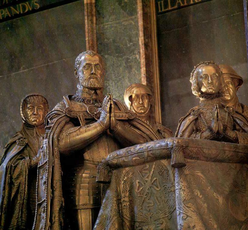 Carlos V, vestido con armadura y amplio manto en el que destaca el águila bicéfala. A su derecha se sitúa su esposa, Isabel de Portugal. Sigue, por detras, María de Austria, hija del Emperador, Doña María de Hungría y doña Leonor de Francia, ambas hermanas de Carlos V.